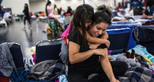 Fresae Oviedo (6)  hugs her mother Nora Pelayo at a temporary shelter at the George R Brown Convention Center in Houston, Texas.  Photograph:   Tamir Kalifa/The New York Times
