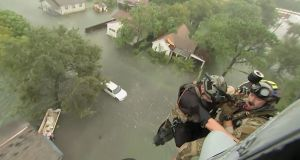 Two rescuers from US Navy Helicopter Sea Combat Squadron 7 are lowered to a house after Tropical Storm Harvey flooded a neighbourhood in Beaumont, Texas. Photograph: US Navy/Reuters