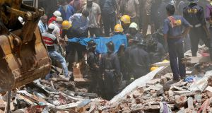 Firefighters and rescue workers remove the body of a victim from debris at the site of a collapsed building in Mumbai, India, on Thursday. Photograph: Shailesh Andrade/Reuters