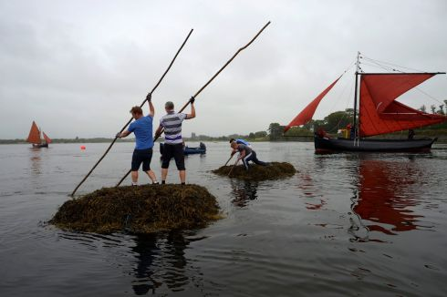 Teams participate in a seaweed race, each pushing a two tonne seaweed bundle known as Climin from the sea to the harbour finish line during Cruinniu na mBad (gathering of the boats) regatta in Kinvara, Ireland, August 20, 2017.