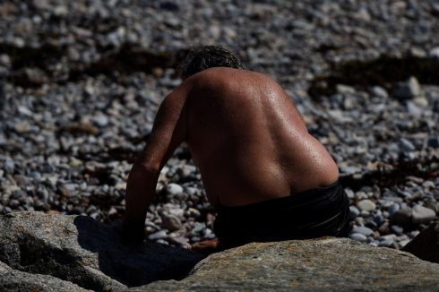 A man sits on the beach during sunny weather in Galway, Ireland, July 17, 2017.
