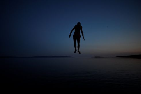 A man jumps off a diving board at night in Salthill, County Galway, Ireland, July 17, 2017.