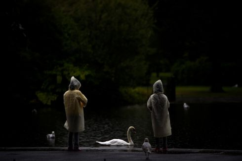 People in raincoats  look at a swan in St. Stephen's green during heavy rain in Dublin, Ireland, August 14, 2017.