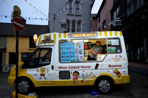 A seller in an ice-cream van waits for customers at night, in the County Kerry town of Killorglin, Ireland, August 10, 2017.