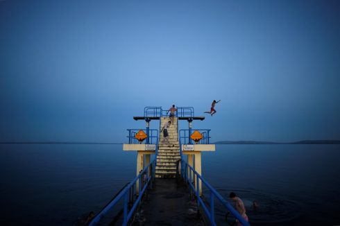 A man jumps off a diving board at night in Salthill, County Galway, Ireland, July 17, 2017.  All photographs by Clodagh Kilcoyne/ Reuters