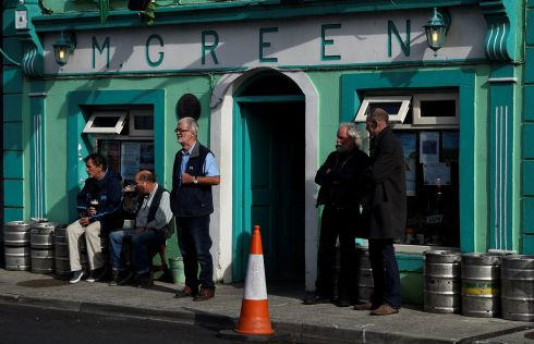 People stand outside a pub in the County Galway town of Kinvara, Ireland, August 19, 2017.