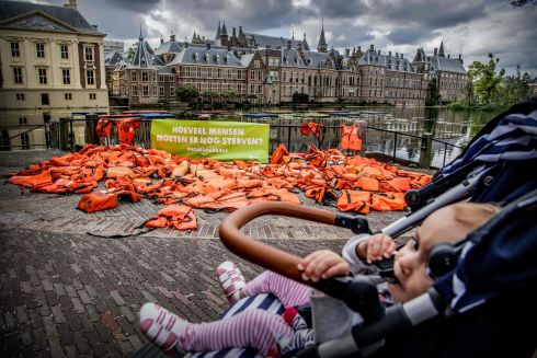 REFUGEE CRISIS: A baby passes by life-jackets displayed in front of the Dutch parliament by Oxfam Novib to highlight the suffering of refugees. Photograph: Robin Utrecht/AFP/Getty Images