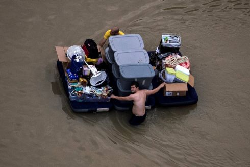 TROPICAL STORM HARVEY: Residents wade with their belongings through flood waters in northwest Houston, Texas, US. Photograph: Adrees Latif/Reuters