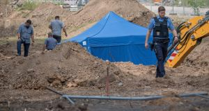 A policeman near a blue tent covering a British second World War  bomb  found during construction works  in Frankfurt,  Germany. The disposal of the bomb planned for this Sunday requires the evacuation of tens of thousands of people. Photograph: Boris Roessler/AFP/Getty Images