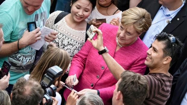 Angela Merkel poses for a selfie with a supporter in Berlin last month. Photograph: Clemens Bilan/EPA