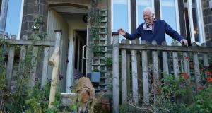 Tony Booth at home in his garden in West Yorkshire, England, with his  rescue lurcher, Eddie