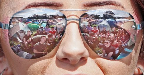 A group of revellers reflected in a womans sunglasses as crowds arrive for the Electric Picnic festival in Stradbally, County Laois.  Photograph: Niall Carson /PA