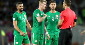 Ireland's James McClean disputes a booking with the referee as Shane Long and Jon Walters  look on. Photograph: Ryan Byrne/Inpho