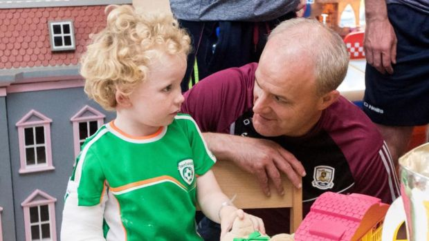 All-Ireland champions: Galway manager Micheál Donoghue with James Dylan at Our Lady's Children's Hospital, in Crumlin. Photograph: Oisin Keniry/Inpho