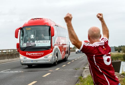 VICTORY SPIN: The bus with the victorious Galway team carrying the Liam MacCarthy Cup passes over the River Shannon in Athlone as Timmy Ó Flatharta from Spiddal salutes, the day after the All-Ireland hurling final win over Waterford. Photograph: James Crombie/Inpho