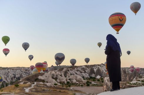 UP, UP AND AWAY: Hot air balloons glide during a flight over Nevsehir in Turkey's Cappadocia region, Central Anatolia, eastern Turkey. Cappadocia has been listed as a World Heritage Site since 1985. Photograph: Yasin Akgul/AFP/Getty Images