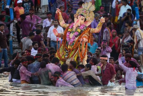 GANESH FESTIVAL: Indian Hindu devotees carry an idol of the elephant-headed Hindu god Lord Ganesha for immersion in a pool near Sangam in Allahabad. Photograph: Sanjay Kanojia/AFP/Getty Images