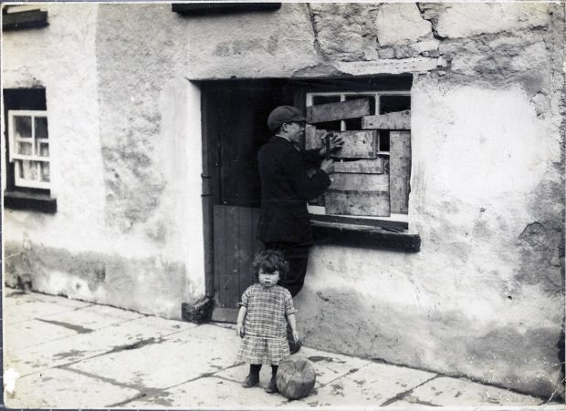 A boy boards up a window in Templemore, Co Tipperary, in 1920 after a British military reprisal. Photograph: Courtesy of National Library of Ireland