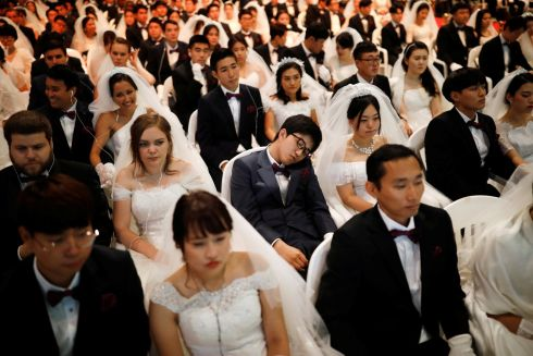 MARITAL BED: A groom naps as couples attend a mass wedding ceremony of the Unification Church, at CheongShim Peace World Centre in South Korea. Photograph: Kim Hong-ji/Reuters