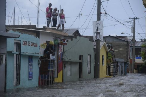 HURRICANE IRMA: People look down on a flooded street from a roof in Santiago de los Caballeros, Dominican Republic, after the passage of Hurricane Irma. Photograph: Luis Tavarez/EPA