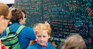 People writing on the #SoundEffect 'Wall of Sound' at Electric Picnic 2017