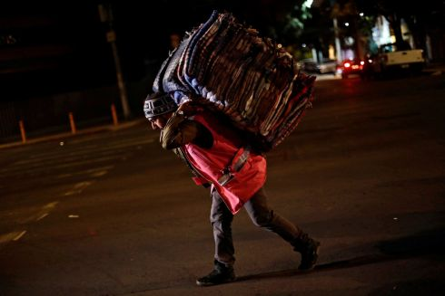 A volunteer carries blankets in Mexico City. Photograph: Edgard Garrido/Reuters