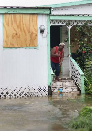 A woman pushes out floodwaters on her property after the passing of Hurricane Irma, in St. John's, Antigua and Barbuda.  Photograph: Johnny Jno-Baptiste / AP