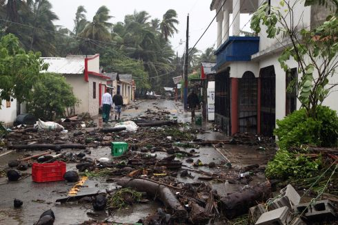People walk on a street covered in debris as Hurricane Irma moves off from the northern coast of the Dominican Republic, in Nagua. Photograph: Ricardo Rojas/Reuters