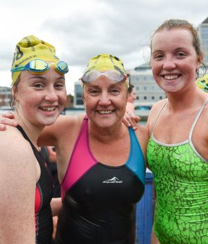 Women's race winner Anne Marie Bourke from Dublin with children Heather, left, and Alison, right, following the Liffey Swim.  Photograph: Ramsey Cardy/Sportsfile
