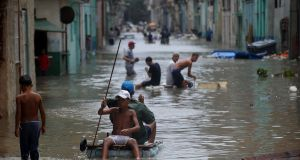 Cubans wade through a flooded street in Havana. Photograph: Yamil Lage/AFP/Getty Images