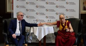 The Dalai Lama holds the hand of Richard Moore at a Children in Crossfire press conference  in Derry, Northern Ireland. Photograph: Charles McQuillan/Getty Images