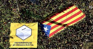 Thousands of people carry a giant Catalan independence flag and a banner reading 'Referendum is Democracy', in Barcelona,  Spain. Photograph: Roser Vilallonga/ Catalan National Assembly/EPA