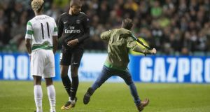 A pitch invader tries to kick Kylian Mbappé during Celtic's 5-0 thrashing a tthe hands of PSG. Photograph: Steve Welsh/Getty