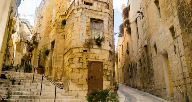 The narrow streets of the Collachio – the ancient part of the city – in Vittoriosa, which is full of charming houses and auberges, framed in colourful bougainvillea, oleander and jacaranda. Photograph: Getty Images