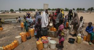 Displaced people collect water in Muna Garage camp for the displaced on the outskirts of Maiduguri, northeast Nigeria. Photograph: Sally Hayden