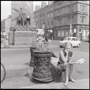 A  woman sits beside ornate ironwork bollards, at the Parnell Monument, O'Connell Street, Dublin. Photograph: Unknown