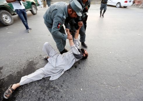 AFGHAN ATTACK: Afghan police officers comfort a man after he received news of his relatives being among the victims of a suicide attack, in Kabul. Photograph: Mohammad Ismail/Reuters