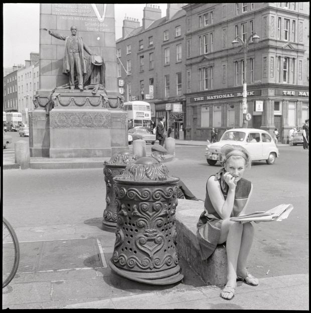 Bollards – Woman sitting beside ornate ironwork bollard on O'Connell Street, Dublin, June or July 1969