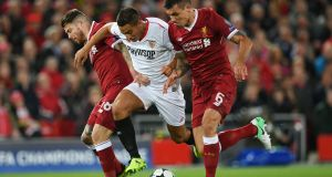 Alberto Moreno and Dejan Lovren try to make a tackle against Sevilla at Anfield. Photograph: Getty Images