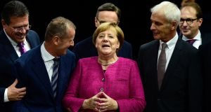 German Chancellor Angela Merkel (C) is flanked by Volkswagen chairman Matthias Mueller (C-R) and Volkswagen board member Herbert Diess (C-L) as she visits the booth of Volkswagen (VW) at the Frankfurt motor show