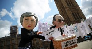 Protesters depicting media magnate Rupert Murdoch and British prime minister Theresa May demonstrate opposite the Houses of Parliament in London on Tuesday. Photograph: Hannah McKay / Reuters.