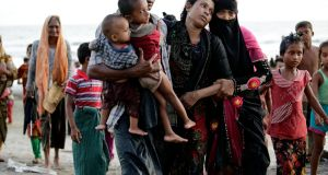 Sick Rohingya woman Anowara Begum along with her husband and children after disembarking from a boat that crossing Naf river and landed in Teknaf, Bangladesh, on Thursday. Photograph: Abir Abdullah/EPA