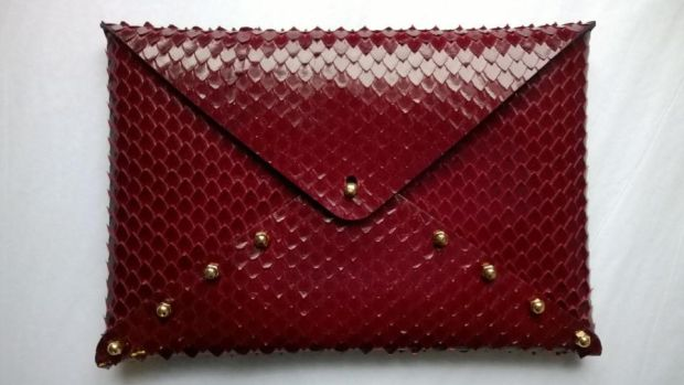 A red snakeskin style clutch in calfskin with brass fitting by Una Burke