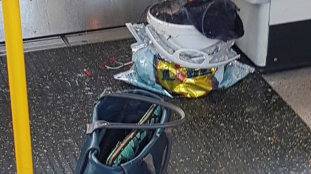 Personal belongings and a bucket with an item on fire inside it on the floor of an underground train carriage at Parsons Green station in west London.