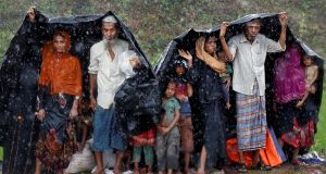 Rohingya refugees shelter from the rain in a camp in Cox's Bazar, Bangladesh. Photograph:  Reuters/Cathal McNaughton