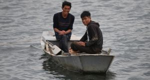 Two North Korean men smile on the Yalu river opposite the Chinese border city of Dandong. Photograph: Greg Baker/AFP/Getty Images
