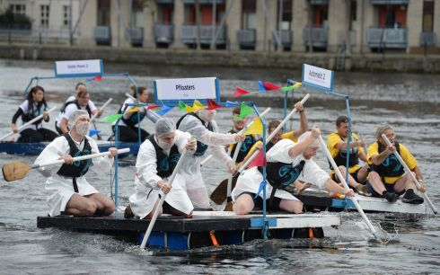 MAKING WAVES: Participants in the Raft Race Against Homelessness powering their rafts around a course in Grand Canal Dock. Photograph: Dara Mac Donaill/The Irish Times