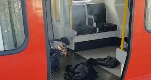 Personal belongings and a bucket with an item on fire inside it are seen on the floor of an underground train carriage at Parsons Green station in West London