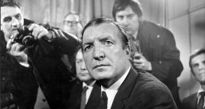 Charles Haughey is flanked by photographers at a press conference in Dublin, following his acquittal in the Arms Trial in October 1970