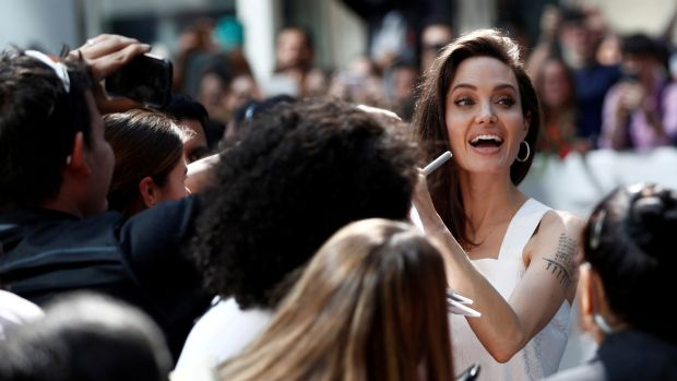 "Executive producer Angelina Jolie signs autographs on the red carpet for the film ""The Breadwinner"". REUTERS/Mark Blinch/File Photo"
